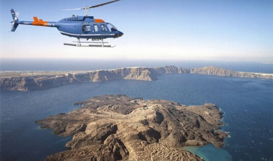 A guest of the luxury suite of Nostos Apartments is having a helicopter tour in Oia Santorini