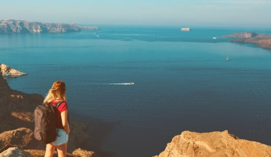 A guest of the luxury apartment of Nostos Apartments is having a hiking tour in Oia Santorini